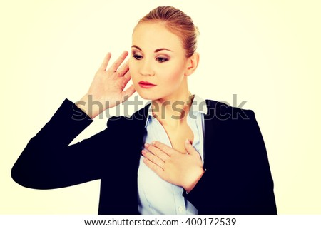 Young shocked business woman overhears a conversation - stock photo