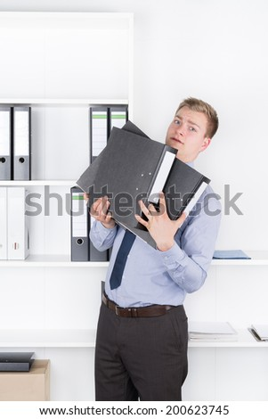 Young shocked businessman is holding several files in his arms while standing in front of a shelf in the office. The man is looking to the camera. - stock photo