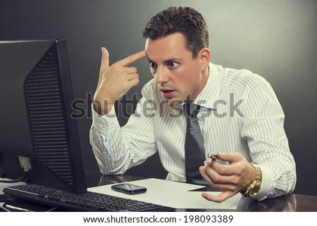 Young shocked desperate businessman in white shirt and tie pointing his finger to his head in a shoot himself gesture after receiving bankruptcy news in front of his computer at work. - stock photo