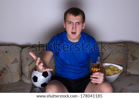 young shocked emotional supporter in uniform sitting on the sofa and watching football with beer and chips - stock photo