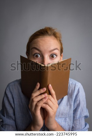 Young shocked girl with book. Learn something. - stock photo