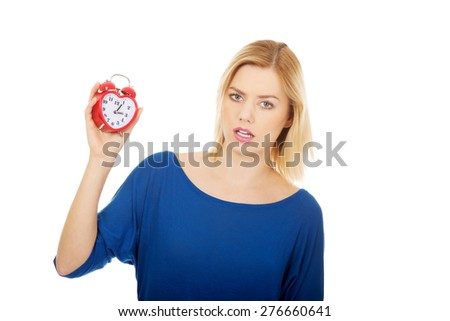 Young shocked woman holding a clock.
