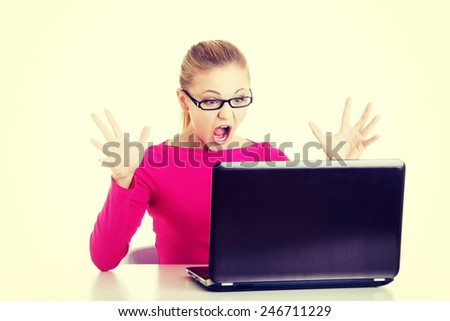 Young shocked woman sitting in front of laptop. - stock photo