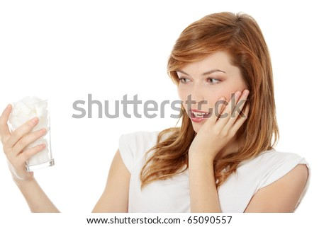 Young shocked woman with lot of sugar in glass. Lot of calories in drink - stock photo