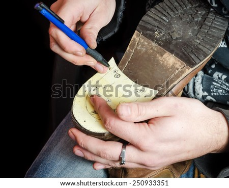 Young shoemaker making a new drafts for new pair of shoes heel - stock photo