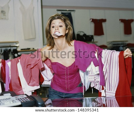 Young shopaholic woman loaded with clothes holding credit card in mouth at store - stock photo