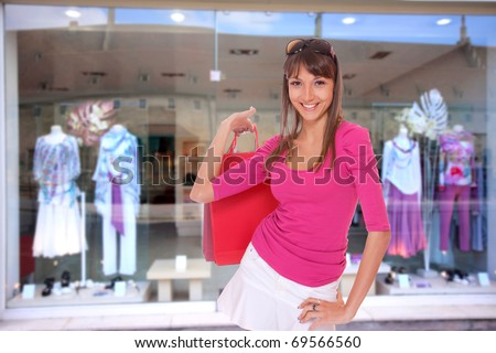 Young shopping woman in front of the shop - stock photo