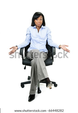 Young shrugging confused black businesswoman sitting in leather office chair