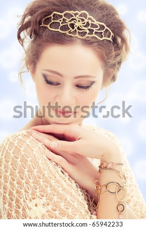 Young shy woman in a diadem and bracelets of gold on abstract background. - stock photo