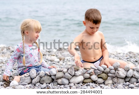 Young Siblings on Holiday Building Stone Wall Together on Rocky Beach with View of Water in Background - stock photo