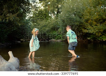 Young siblings playing in river, exploration concept