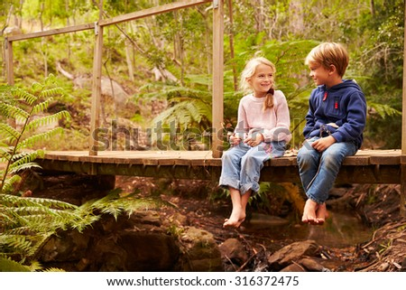 Young siblings sitting on a bridge in a forest - stock photo