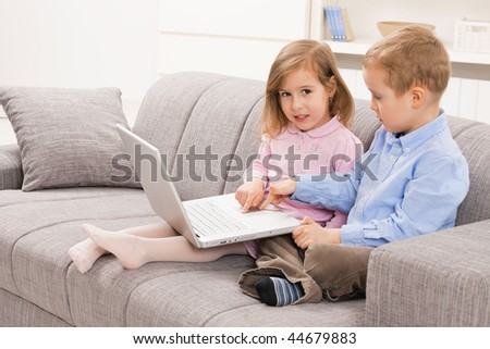 Young siblings sitting on couch at home, browsing internet on laptop computer, smiling. - stock photo