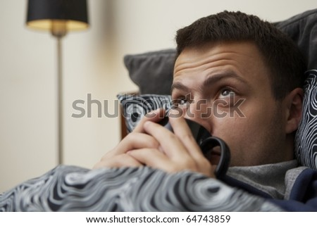 Young sick man in the bed and drinking tea. - stock photo