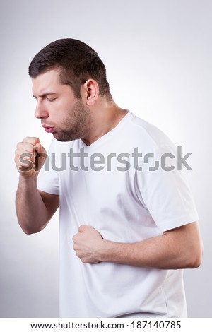 Young sick man in white t-shirt coughing - stock photo
