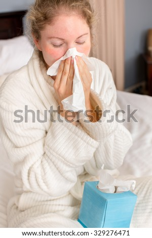 Young sick woman holding tissue sitting  in bed - stock photo