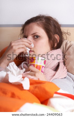 Young sick woman lying in bed. She is staying home from work. - stock photo
