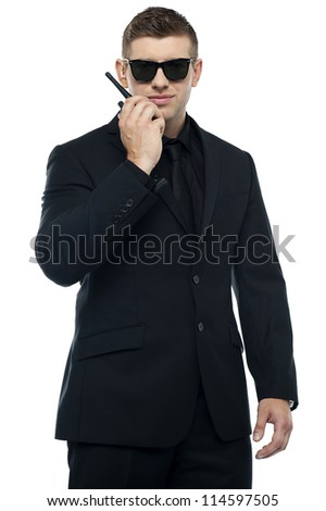 Young sincere security officer talking through his walkie talkie isolated over white background. Half length portrait - stock photo