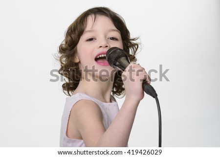 Young singer performs her song. Little girl sings in the microphone she holds in her hands. Opened mouth and fiery eyes while recording her new song in the studio.