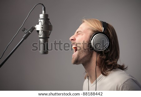 Young singer recording a song - stock photo