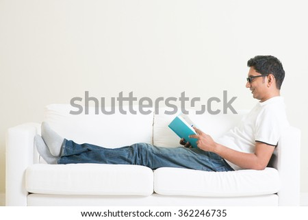 Young single Indian guy reading book and rest at home. Asian man relaxed on sofa indoor. Handsome male model. - stock photo