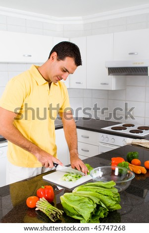 young single man cooking in modern kitchen - stock photo