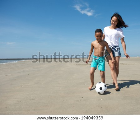 Young single mother playing with ball together with son on the beach  - stock photo