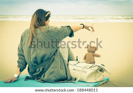 Young single woman sitting at the beach with her teddy bear looking at the sea - Vintage retro nostalgic filtered look - stock photo