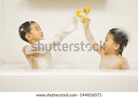 Young sister and brother playing with rubber duck in bathtub - stock photo