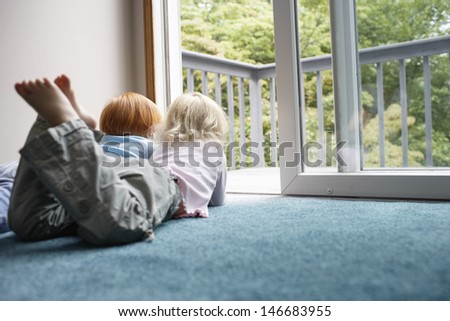 Young sisters looking out through balcony while lying on carpet at home - stock photo