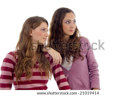 young sisters looking sideways on an isolated background - stock photo