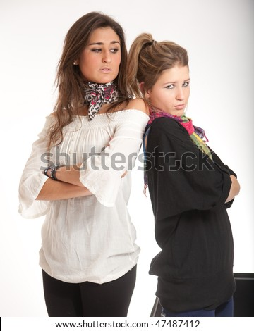 Young sisters one blond the other brunette angry with each other - stock photo