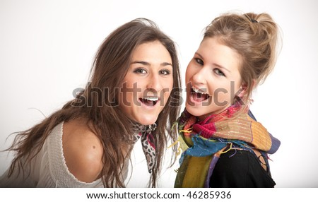 Young sisters one blond, the other brunette laughing together - stock photo