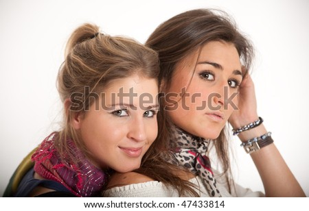 Young sisters one blond, the other brunette on an embrace - stock photo