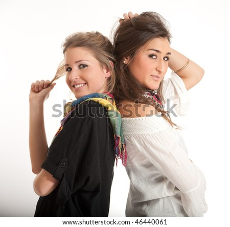 Young sisters, one blonde, the other brunette posing back to back - stock photo