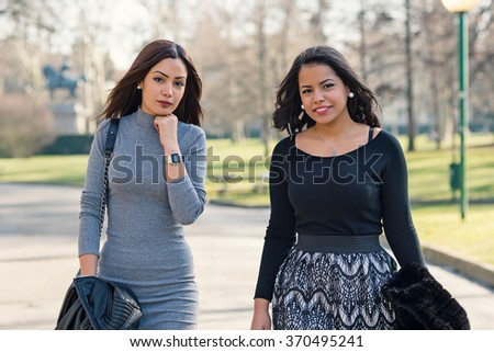 Young sisters walking together in the park. - stock photo