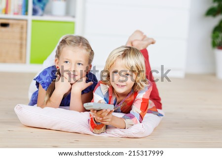 Young sisters watching television while lying on mattress at home - stock photo