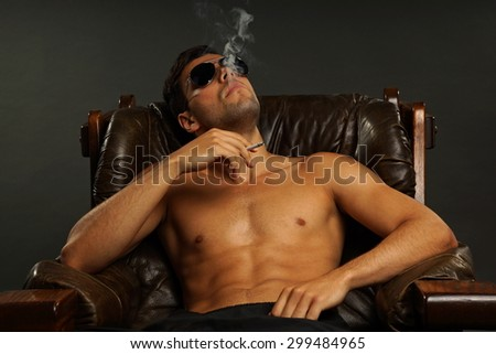 Young sitting man in sunglasses smoking a cigarette on gray background