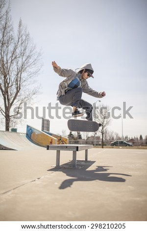 Young skateboard enthusiast in skatepark doing a kickflip - stock photo