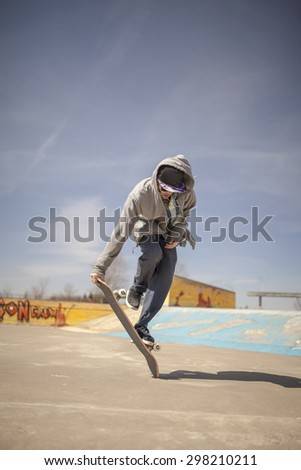Young skateboard enthusiast in skatepark doing old school tricks - stock photo