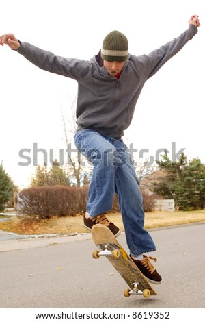 Young skateboarder doing an ollie. - stock photo