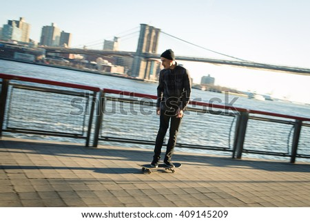 Young skateboarder in casual clothes cruise down on pedestrian walk in New York City.