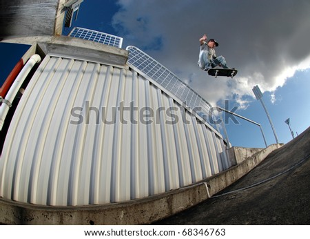 Young skateboarder jumping over a handrail on a parking lot
