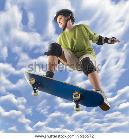 Young skateboarder make a jump on skateboard. Unusual angle view - directly below. - stock photo