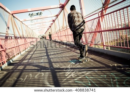 Young skateboarder speed through the pedestrian walkway on Williamsburg Bridge, NYC. Photographed in Feb 2016.