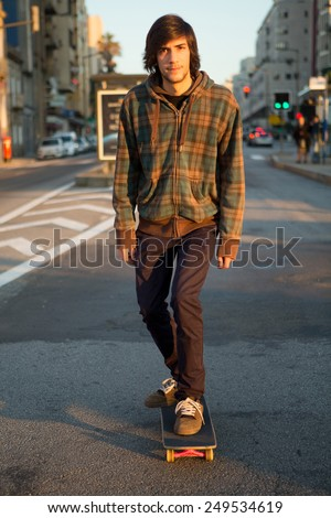 Young skater cruising the city center at the end of the day - stock photo