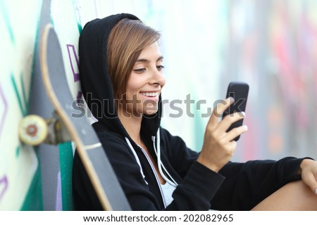 Young skater happy teen girl using a smart phone with a blurred graffiti wall in the background         - stock photo