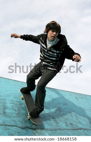 Young skater performing stunts in a blue skate bowl - stock photo