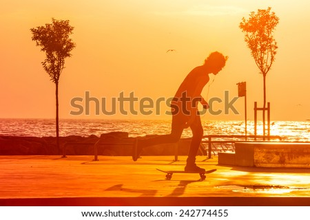 Young skaters training in the park near the sea in sunset. Toned picture - stock photo