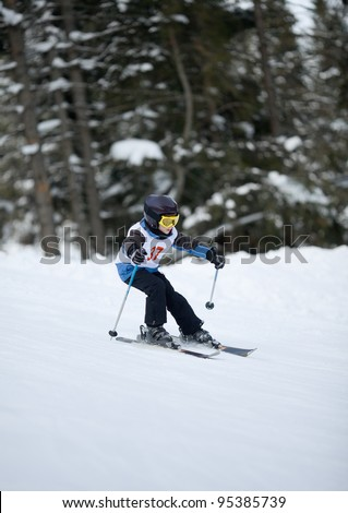 Young skier at downhill slalom competitions - stock photo
